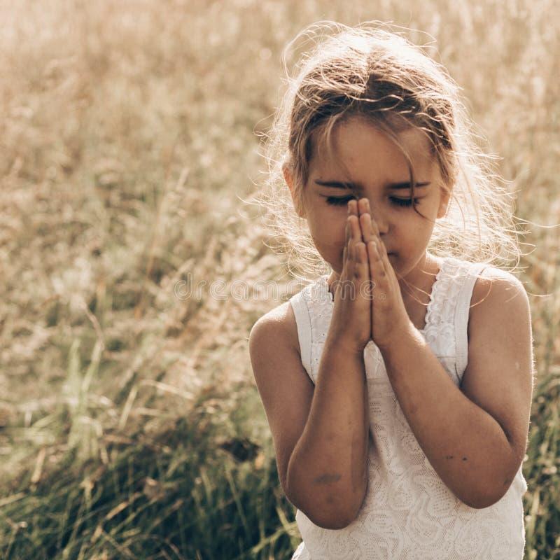 Het meisje sloot haar ogen biddend bij zonsondergang Handen in gebedconcept worden gevouwen voor geloof, spiritualiteit en godsdi royalty-vrije stock afbeelding