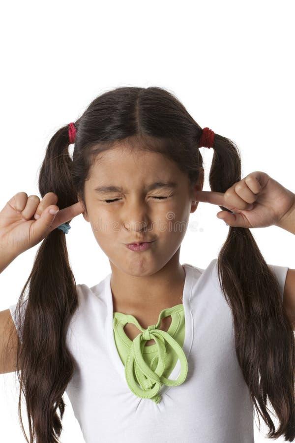 Het meisje sluit haar oren met haar vingers stock foto's