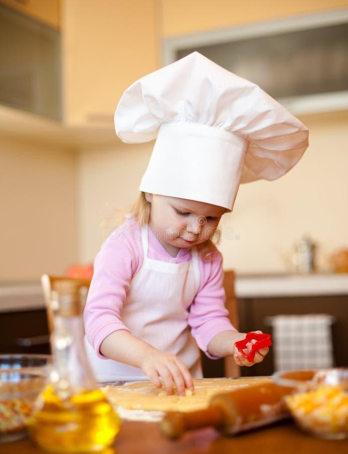 Het meisje snijdt deeg voor koekjes op keuken stock foto