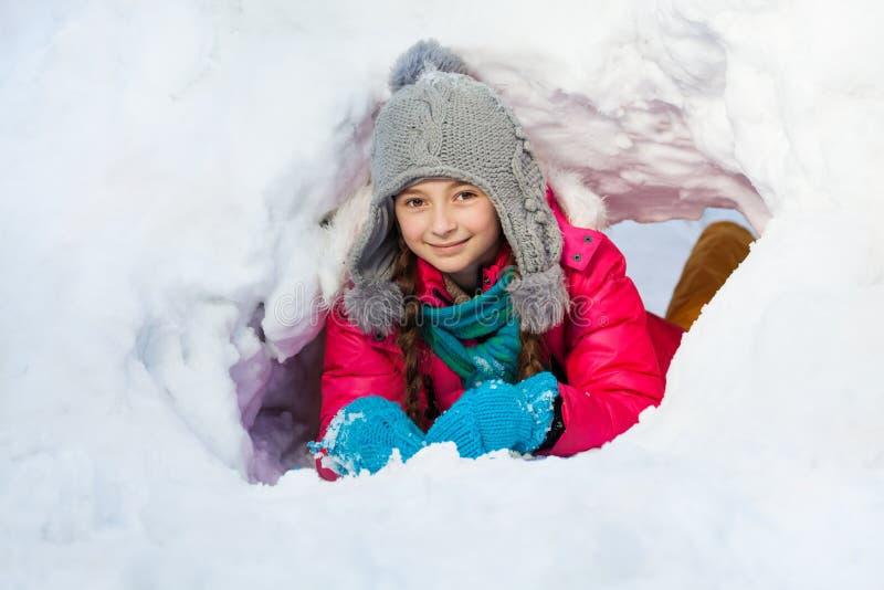 Het meisje speelt buiten in tunnel die zij van sneeuw heeft gegraven royalty-vrije stock foto