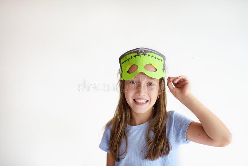 Het meisje speelt de dwaas in een masker van het monster stock afbeelding