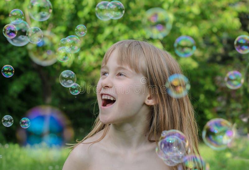 Het meisje speelt en geniet van zeepbels in de binnenplaats stock foto