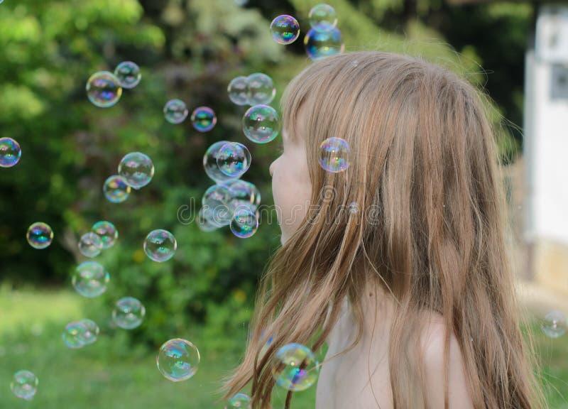 Het meisje speelt en geniet van zeepbels in de binnenplaats royalty-vrije stock foto's