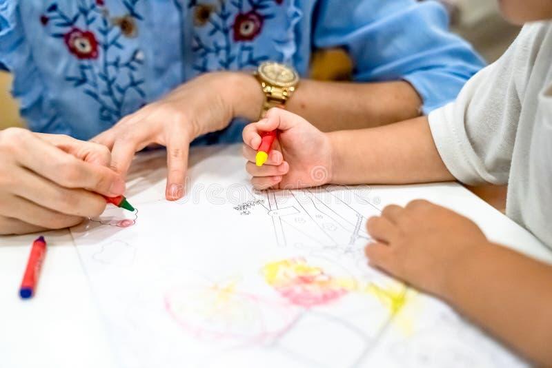 Het meisje speelt en leert aan het kleuren van Kleurpotlood op het document in het roomijsrestaurant , Bangkok, Thailand royalty-vrije stock afbeeldingen