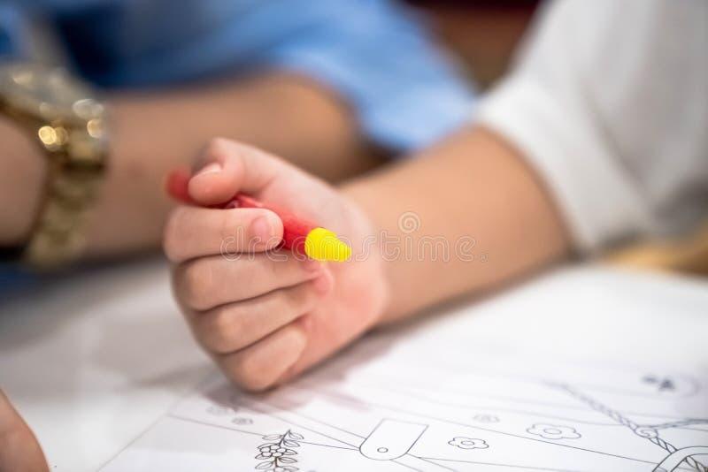 Het meisje speelt en leert aan het kleuren van Kleurpotlood op het document in het roomijsrestaurant , Bangkok, Thailand stock fotografie