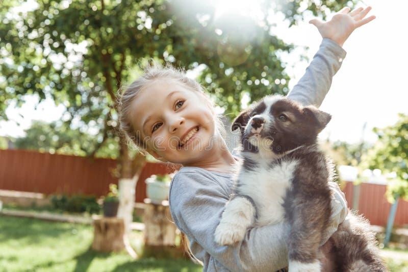 Het meisje speelt met een hond een hond als gift aan kinderen kinderen` s glimlach op de aard royalty-vrije stock afbeelding