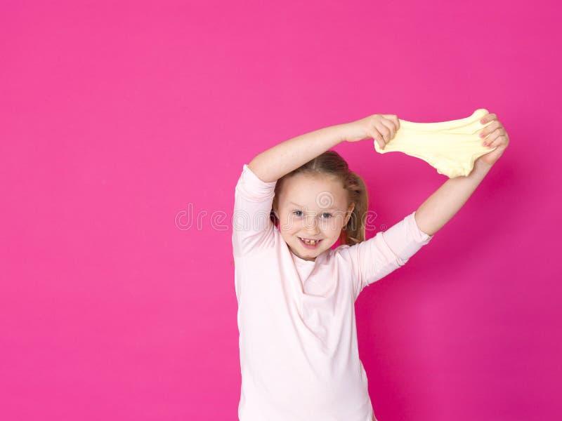 Het meisje speelt met geel slijm voor roze achtergrond royalty-vrije stock foto