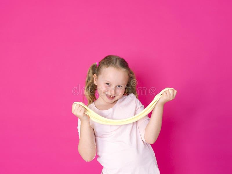 Het meisje speelt met geel slijm voor roze achtergrond stock foto