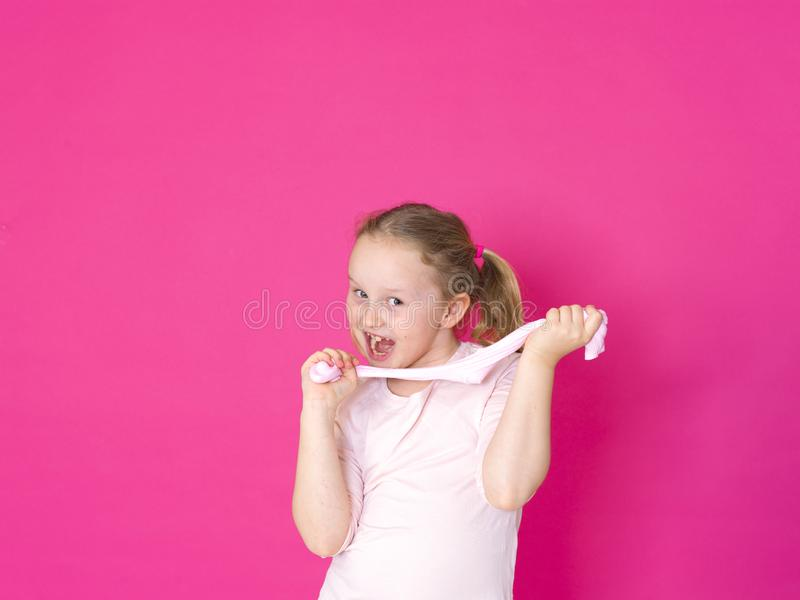 Het meisje speelt met geel slijm voor roze achtergrond royalty-vrije stock foto's
