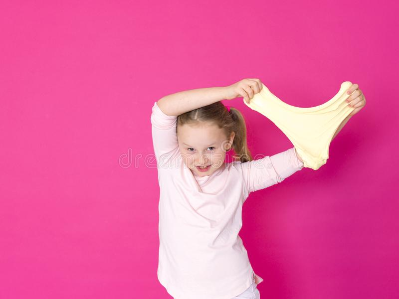 Het meisje speelt met geel slijm voor roze achtergrond stock foto's