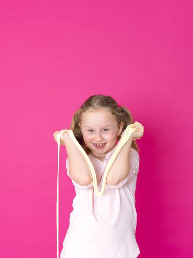 Het meisje speelt met geel slijm voor roze achtergrond royalty-vrije stock fotografie
