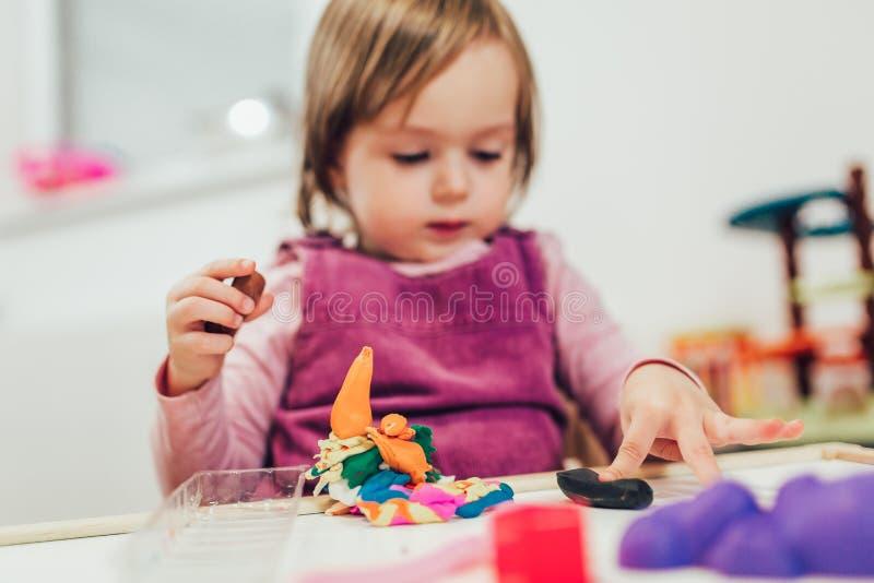 Het meisje speelt met plasticine terwijl het zitten bij lijst in kinderdagverblijfruimte stock fotografie