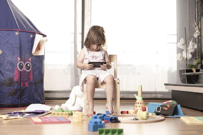 Het meisje speelt Mobiele Telefoon Het Meisje wordt vastgehaakt aan de Mobiele Telefoon Hij speelt niet met speelgoed De mobiele  stock foto's