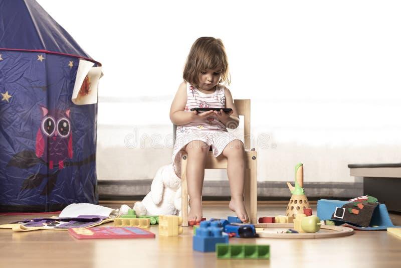 Het meisje speelt Mobiele Telefoon Het Meisje wordt vastgehaakt aan de Mobiele Telefoon Hij speelt niet met speelgoed De mobiele  stock foto