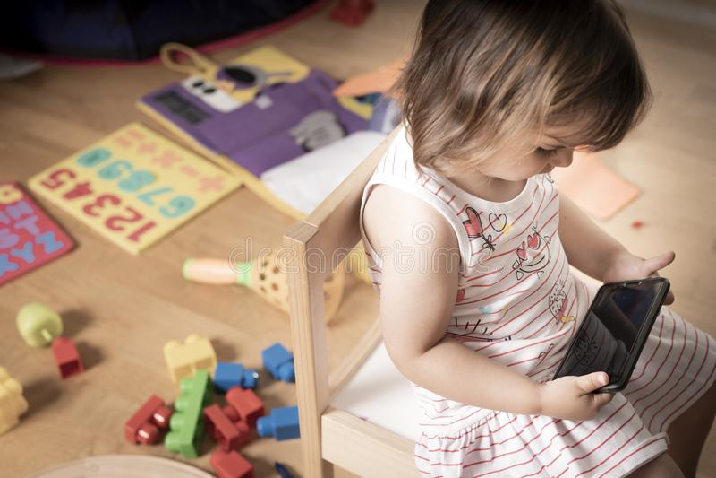 Het meisje speelt Mobiele Telefoon Het Meisje wordt vastgehaakt aan de Mobiele Telefoon Hij speelt niet met speelgoed De mobiele  stock afbeelding