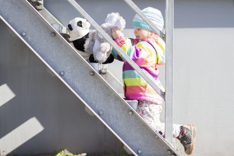 Het meisje speelt op metaaltrap met pluchespeelgoed Babymeisje in gekleurde jasje en hoedenspelen dichtbij huis stock afbeelding