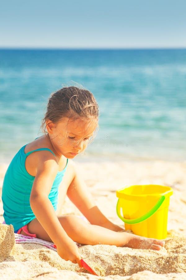 Het meisje speelt op het strand stock afbeelding