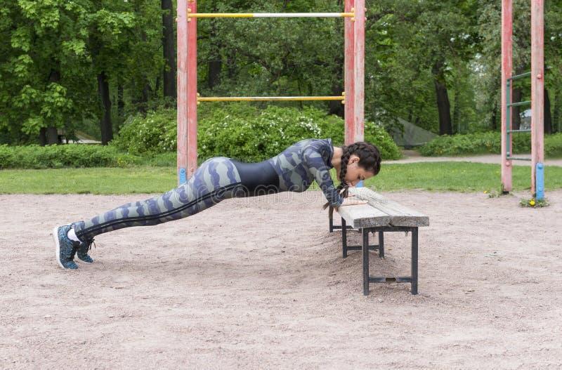 Het meisje in sporten kleedt het doen van opdrukoefeningen van een bank in het Park tegen de achtergrond van groen royalty-vrije stock foto
