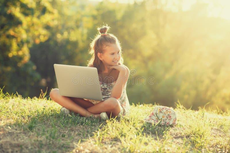 Het meisje spreekt op laptop terwijl het zitten op het gras in de zon Gekleed in sarafan en een hoed stock foto