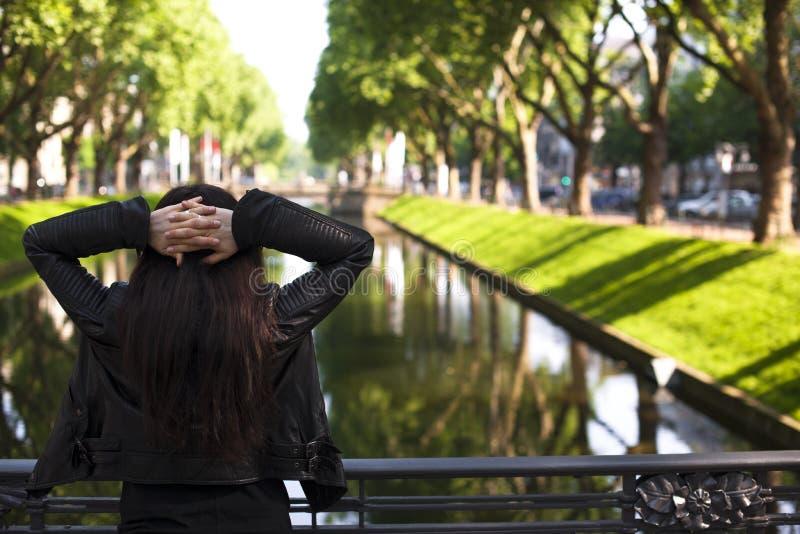 Het meisje stelt op de weg door de rivier in de stad, groene bomen met nadruk op de Verrekijkers De ruimte van het exemplaar royalty-vrije stock afbeelding