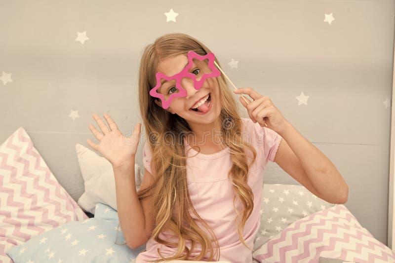 Het meisje stelt in slaapkamer weinig gelukkig meisje met partijglazen de gelukkige emoties van het kindaandeel Zuivere Vreugde royalty-vrije stock fotografie