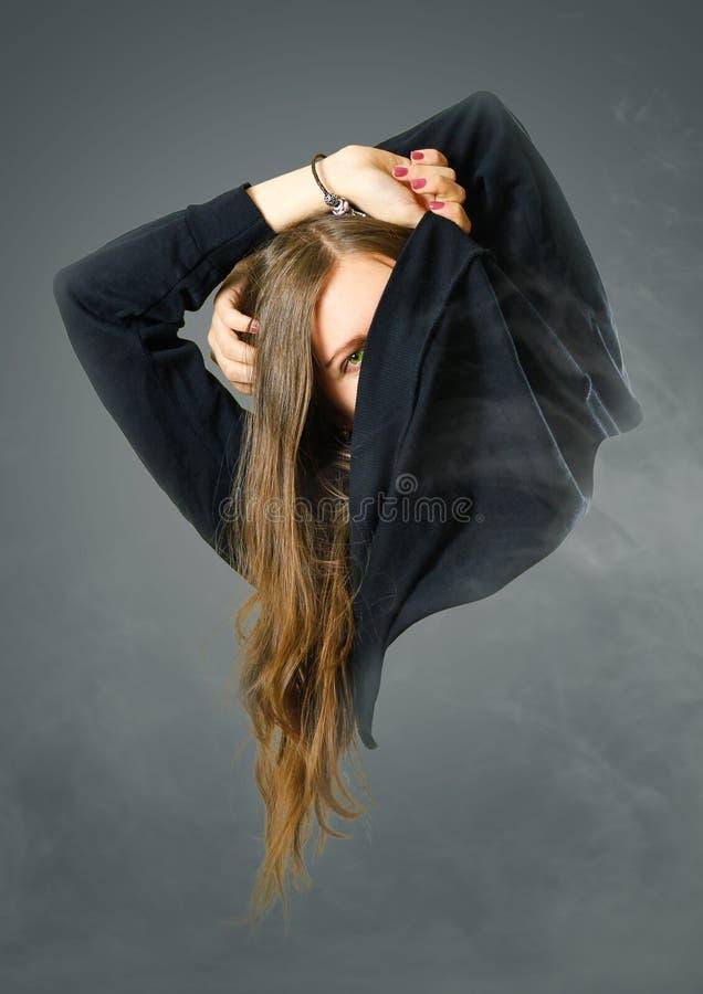 Het meisje stijgt haar zwart jasje op Lege binnenkant royalty-vrije stock foto's
