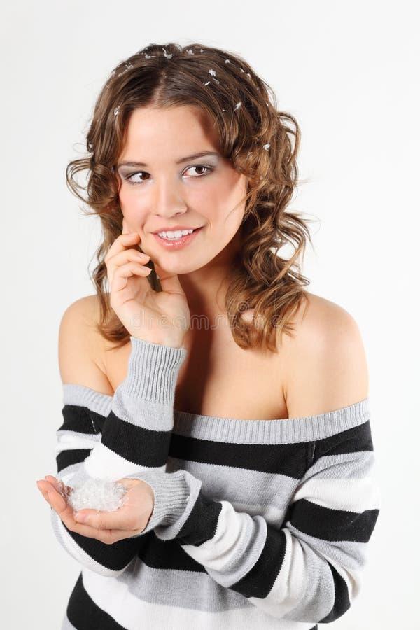 Het meisje in sweater met haar in sneeuw houdt sneeuw in palm royalty-vrije stock afbeelding