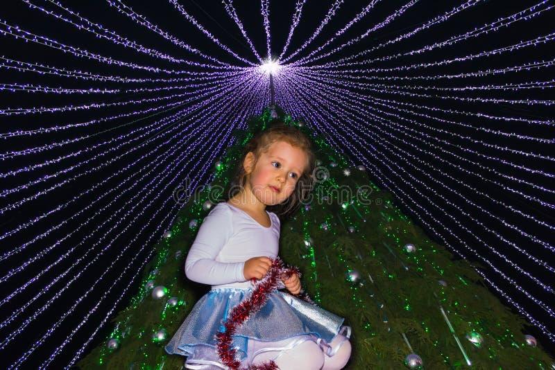 Het meisje tegen verfraaide Kerstmisbomen met lichten stock afbeelding