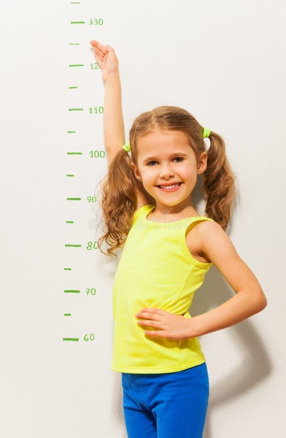 Het meisje toont hoe zij dit jaar zal groeien stock afbeelding