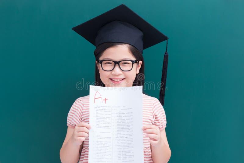 Het meisje toont A plus document stock foto's