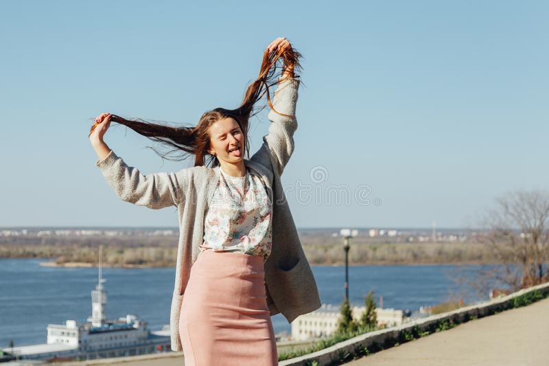 Het meisje toont tong met een open mond en heft het haar op royalty-vrije stock afbeeldingen