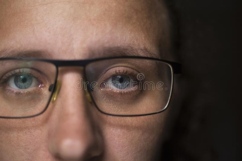 Het meisje in transparante glazen onderzoekt de camera stock foto's