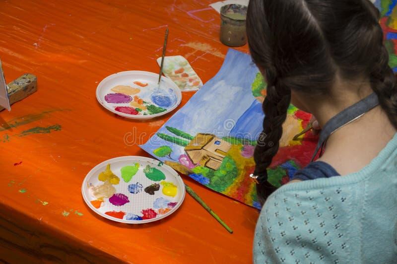 Het meisje trekt een beeld royalty-vrije stock afbeelding