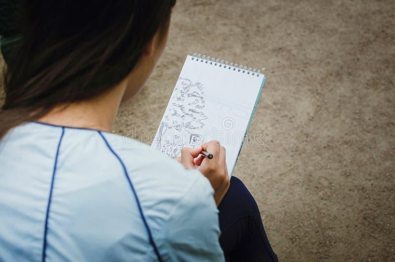 Het meisje trekt in een notitieboekje op de straat Close-up stock afbeelding