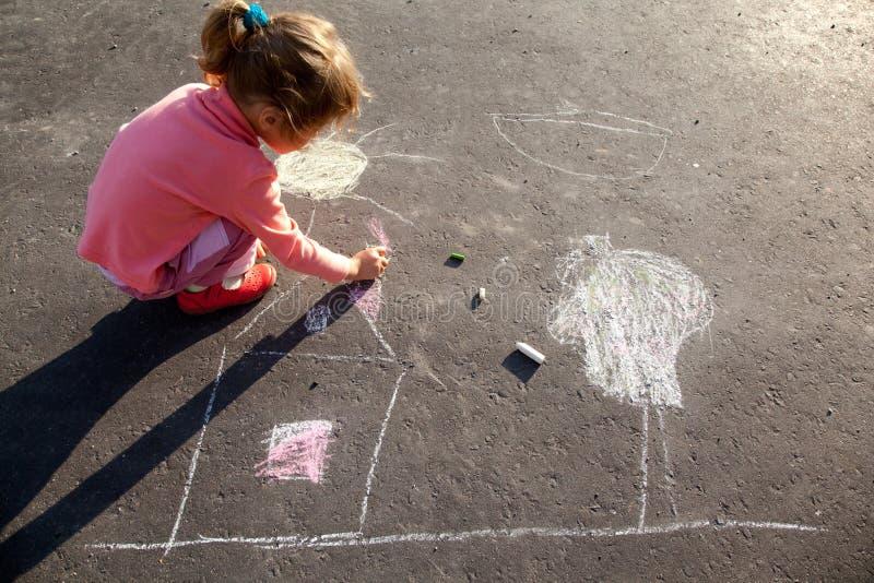 Het meisje trekt het schilderen het krijt van het zonhuis op asfalt