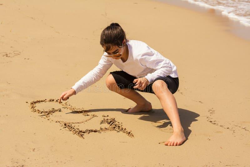 Het meisje trekt I-liefde op het zand royalty-vrije stock afbeeldingen