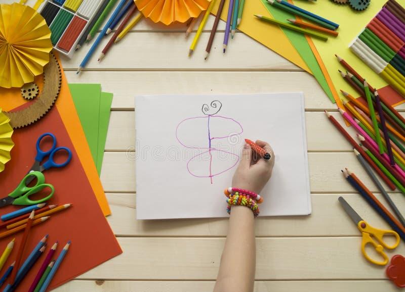 Het meisje trekt Kinderen` s creativiteit Favoriete hobby voor kinderen Materialen en hulpmiddelen Het kind ligt op de vloer en d stock fotografie