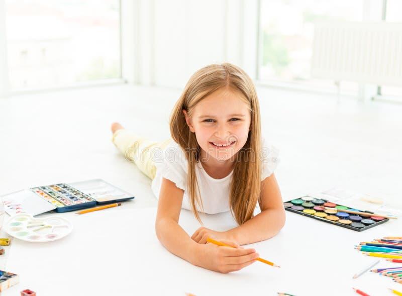 Het meisje trekt het liggen op floorlittle het vrolijke meisje het liggen op de vloer trekt stock foto