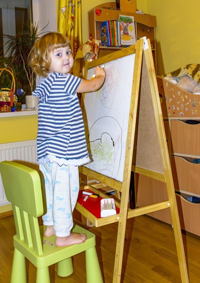 Het meisje trekt op de raad met gekleurde tellers stock foto's