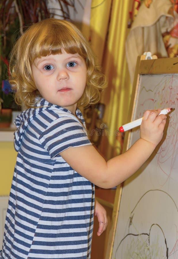 Het meisje trekt op de raad met gekleurde tellers stock foto