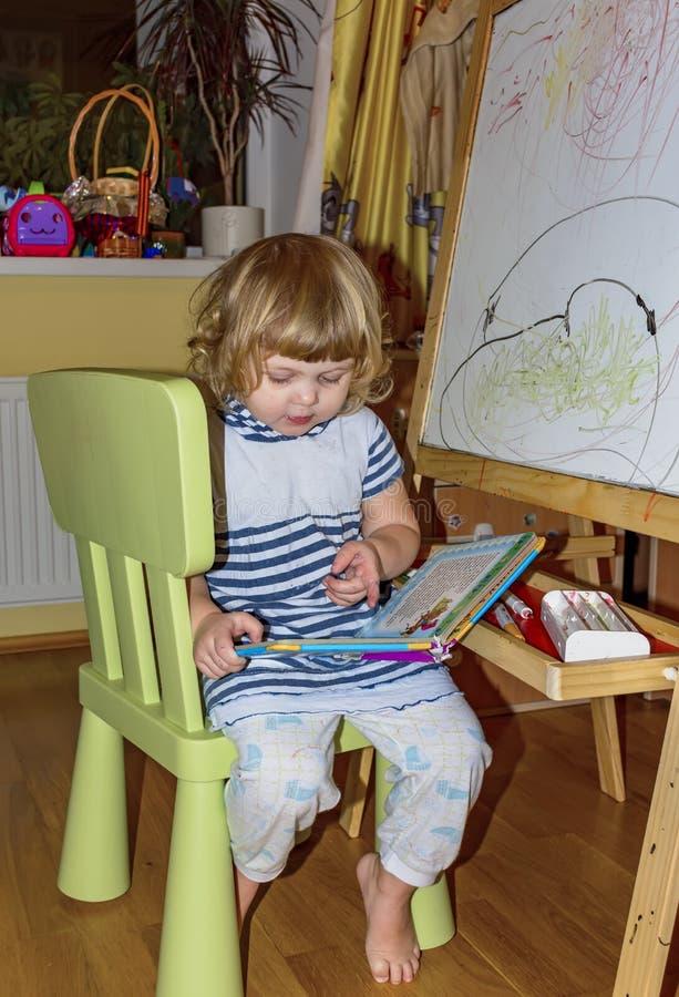 Het meisje trekt op de raad met gekleurde tellers royalty-vrije stock afbeeldingen