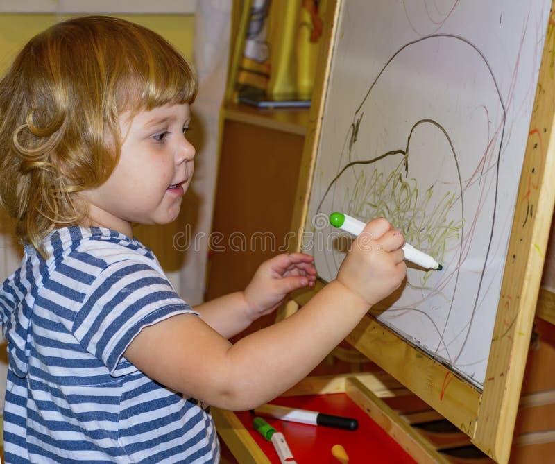 Het meisje trekt op de raad met gekleurde tellers royalty-vrije stock afbeelding