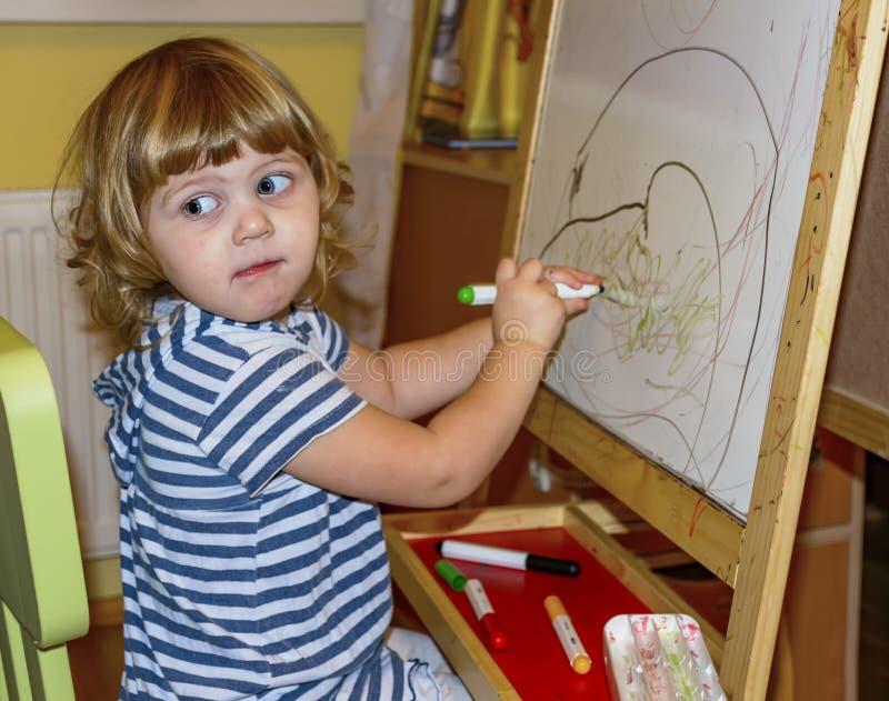 Het meisje trekt op de raad met gekleurde tellers royalty-vrije stock foto's