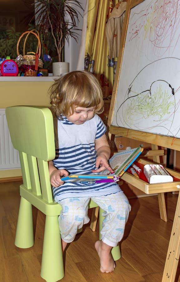Het meisje trekt op de raad met gekleurde tellers stock afbeeldingen