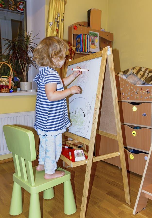 Het meisje trekt op de raad met gekleurde tellers stock fotografie