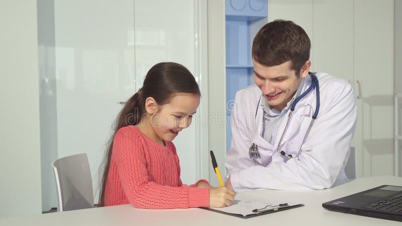 Het meisje trekt op klembord dichtbij de arts royalty-vrije stock foto