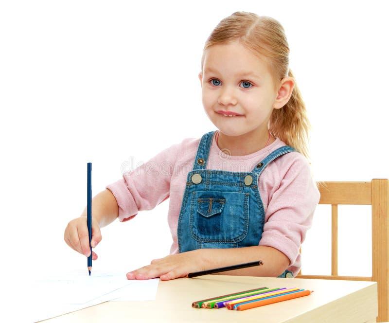 Het meisje trekt potloden zittend bij de lijst stock fotografie