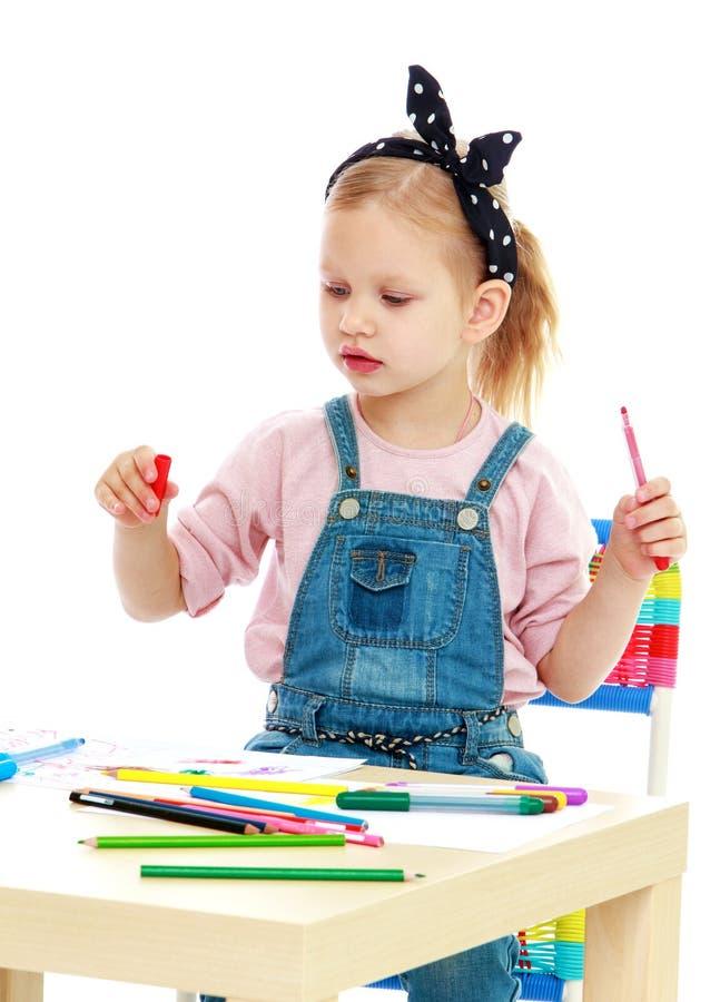 Het meisje trekt potloden zittend bij de lijst stock afbeelding