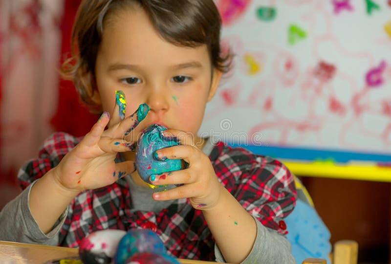 Het meisje trekt vastbesloten de beelden op de eieren met waterverf royalty-vrije stock foto
