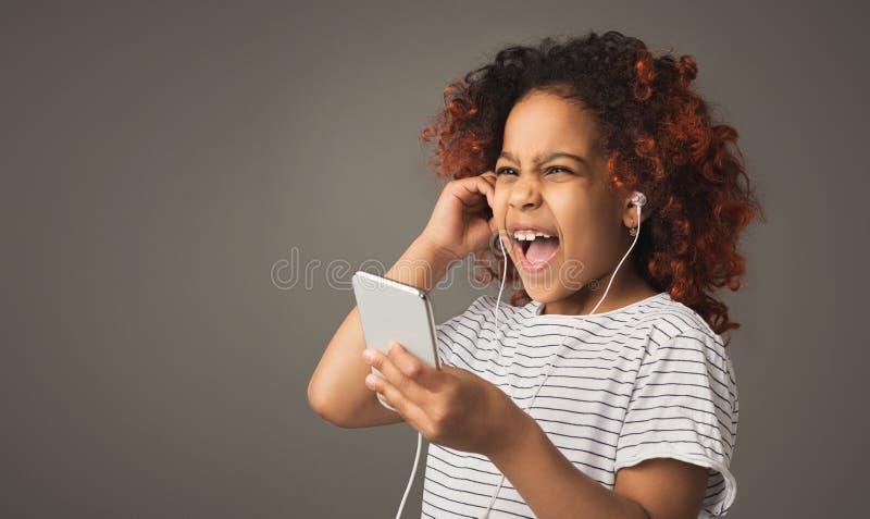Het meisje van het Afrokind in oortelefoons bij grijze studioachtergrond stock afbeelding